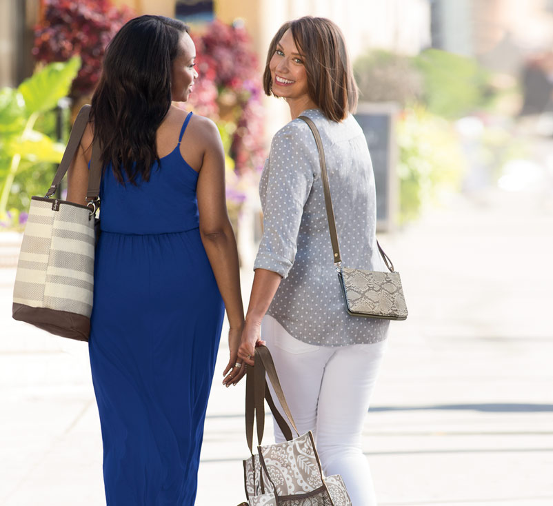 Two women walking with purses and totes